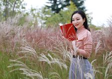 Happy Asian Chinese woman girl feel freedom sweet dream pray flower field autumn fall park grass lawn hope nature read book school. Pink colour grass lawn, rose stock image