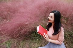 Happy Asian Chinese woman girl feel freedom sweet dream pray flower field autumn fall park grass lawn hope nature read book school. Pink colour grass lawn, rose royalty free stock photo