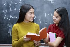 Happy Asian college student reading books in the library tog. Two happy Asian college student reading books in the library together Royalty Free Stock Photography