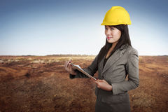 Happy asian contractor woman holding blueprint on clipboard Royalty Free Stock Image