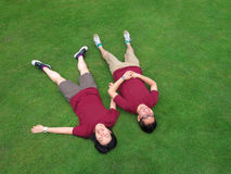 Happy asian couple. A happy asian couple lying down on the grass stock images