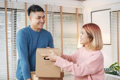 Happy asian couple carry cardboard boxes while moving to new house in living room.unpacking for new home.woman wipe the sweat her stock photography