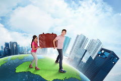 Happy asian couple carrying big suitcase going to travelling. On top of the earth Royalty Free Stock Image