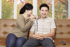 Happy Asian couple on a couch at home Stock Images