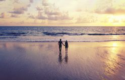 Happy Asian couple dating at the beach during travel honeymoon trip on holidays vacation outdoors. Ocean or nature sea at sunset,. Phuket, Thailand royalty free stock image