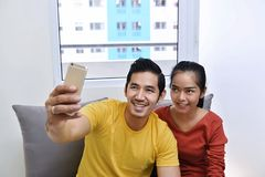 Happy asian couple having fun and taking a selfie. On the couch Stock Photos