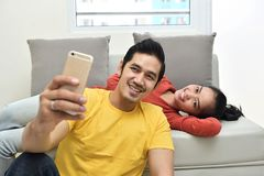 Happy asian couple having fun and taking a selfie. On their aparment Stock Photography