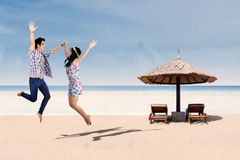 Happy asian couple jumping at beach 1 Royalty Free Stock Image