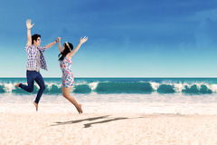 Happy asian couple jumping at beach Royalty Free Stock Photography