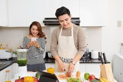 Happy asian couple in love in kitchen making healthy juice.  Stock Photography