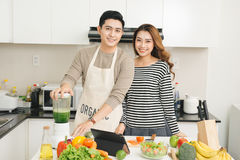 Happy asian couple in love in kitchen making healthy juice Stock Photo