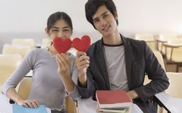 Happy asian couple in love sitting in classroom, holding red heart shape, love symbol.  stock image