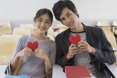 Happy asian couple in love sitting in classroom, holding red heart shape, love symbol.  royalty free stock images