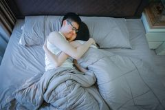 Happy Asian couple in love, sleeping together on bed stock photo