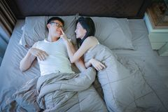Happy Asian couple in love, sleeping together on bed royalty free stock images