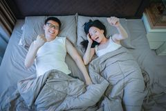 Happy Asian couple in love, sleeping together on bed stock images