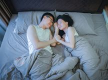 Happy Asian couple in love, sleeping together on bed stock image