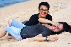 Happy asian couple lying down at beach. Happy and young asian couple lying down at beach and enjoy the vacation Royalty Free Stock Photos