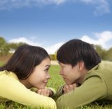 Happy asian couple lying on the grass Royalty Free Stock Photography