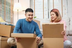 Happy asian couple open cardboard boxes while moving to new home at sofa in living room.unpacking for new house stock photo