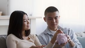 Happy Asian Couple Putting Coin To Piggybank Sitting At Home