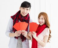 Couple showing red envelope for chinese new year stock photos