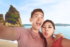 Happy asian couple is taking selfie photo on vacation Stock Image