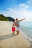 Happy asian couple walking along the beach royalty free stock images