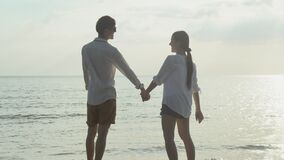 Happy asian couple walking with romantic and holding hand on the beach in summer for leisure together.