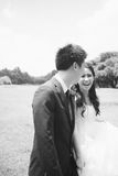 Happy asian couple in wedding dress in a green park Royalty Free Stock Photo