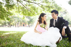 Happy asian couple in wedding dress in a green park Royalty Free Stock Image