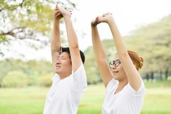 Happy Asian couple in white shirt workout at the park. Couple are smiling and warming up and stretching her arms at outdoors on morning. Health care concept stock photography