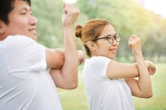 Happy Asian couple in white shirt workout at the park. Couple are smiling and warming up and stretching her arms at outdoors on morning. Health care concept stock photo