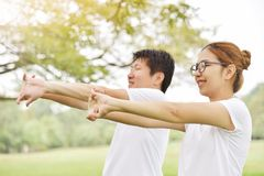 Happy Asian couple in white shirt workout at the park. Couple are smiling and warming up and stretching her arms at outdoors on morning. Health care concept royalty free stock images