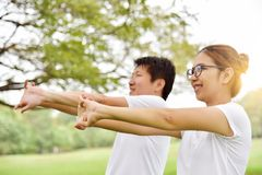 Happy Asian couple in white shirt workout at the park. Couple are smiling and warming up and stretching her arms at outdoors on morning. Health care concept royalty free stock image