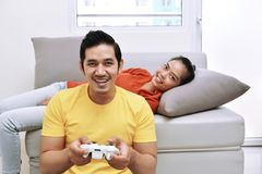 Happy asian couple with the woman lying down on couch and the ma Stock Images