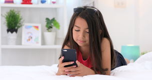 Happy asian cute girl playing on smart phone with smile face at home stock footage