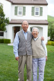 Happy Asian Elderly Couple in front Yard Royalty Free Stock Images