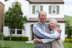 Happy Asian Elderly Couple in front Yard Stock Image