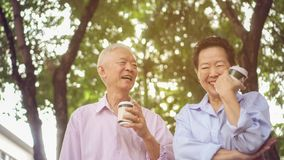 Happy Asian elderly couple morning walk in green city while drin stock photos