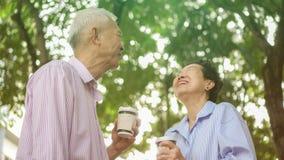 Happy Asian elderly couple morning walk in green city stock photos