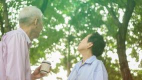 Happy Asian elderly couple morning walk in green city royalty free stock photos