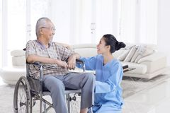 Happy Asian elderly man talking with nurse. Happy Asian elderly men talking and smiling with his nurse while sitting on wheelchair in the living room at home stock photos