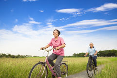 Happy Asian elderly seniors couple biking in farm Stock Photo