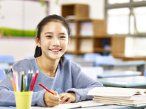 Happy asian elementary school girl. Happy asian elementary school student studying in classroom looking at camera smiling Royalty Free Stock Photography