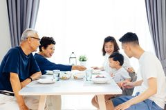 Happy Asian extended family having dinner at home full of laught. Er and happiness Stock Photos