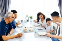 Happy Asian extended family having dinner at home full of laughter and happiness. Happy Asian extended family having dinner at home full of laughter and Royalty Free Stock Photography