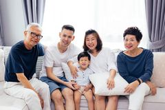 Happy Asian extended family sitting on sofa together, posing for group photos. Happy Asian extended family sitting on sofa together, posing for group photos Royalty Free Stock Photos