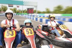 Happy family driving go kart on the track Royalty Free Stock Image