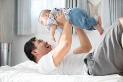 Happy asian family father with baby son playing on bed with smil. Happy asian family father with baby son are playing on bed with smile face Royalty Free Stock Image